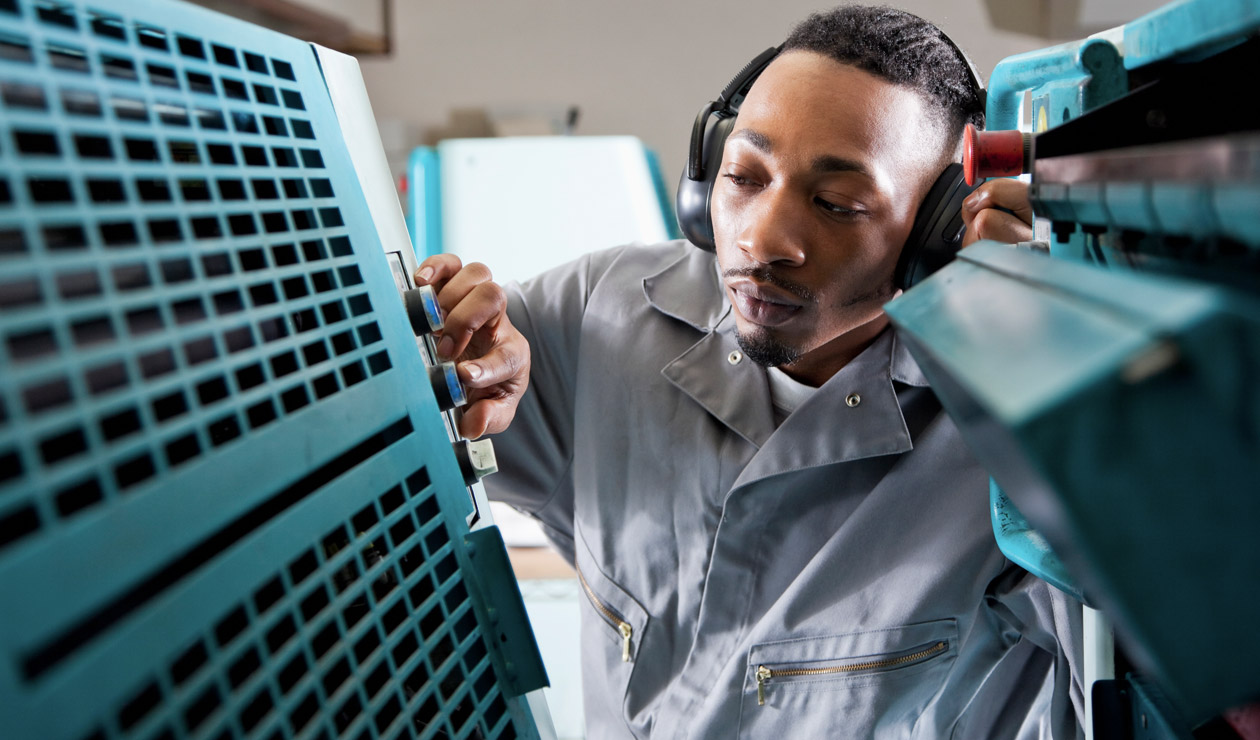 man wearing headphones working in factory